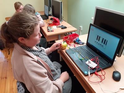 Uczennica siedzi przy biurko. Na biurku leży uruchomiony laptop z wyświetlonym fragmentem klawiatury pianina. Na biurku leżą kolorowe kable: czerwony, zielony żółty i biały. Czerwony kabel podłączony jest do komputera, a końcówka zielonego wbita jest w jabłko leżące na lewo od laptopa. Uczennica dotyka palcami lewej ręki jabłka. Na drugim planie widać podobne stanowisko, przy którym siedzą dwie uczennice.