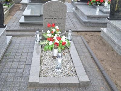 grób wojenny Stefana Karczewskiego strzelca, który poległ w 1939 r. Na grobie kwiaty w kolorze biało-czerwonym oraz cztery znicze.