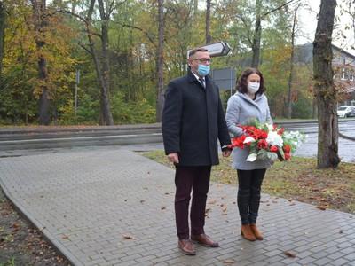 Wójt Gminy Brzeziny Marek Cieślarczyk z Panią Kamilą Biernacik składają kwiaty w kolorze biało-czerwonym przy pomniku upamiętniającym żołnierzy z tereny gminy Brzeziny poległych podczas II Wojny Światowej