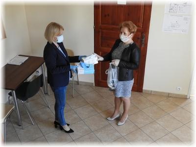 Kierownik GOPS Orchowo Iwona Mietlicka przekazuje zestaw maseczek oraz rękawic ochronnych dla podopiecznych w związku z zabezpieczeniem przed rozprzestrzenianiem się epidemii koronawirusa COVID 19
