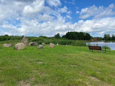 Zdjęcie przedstawia Jezioro w Ostrowcu latem, teren zielony, kamienie oraz ławeczkę.