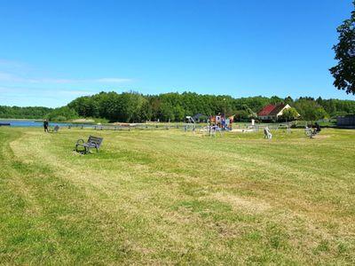 Zdjęcie przedstawia teren rekreacyjny, plac zabaw w kształcie statku przyJeziorze w Ostrowcu wiosną.