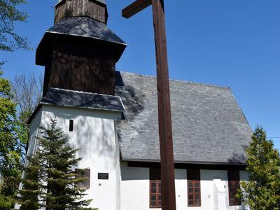 Zdjęcie przedstawia kościół w Karwicach i krzyż na pierwszym planie.