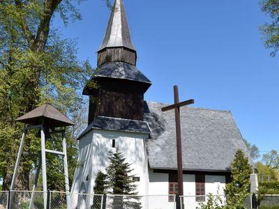 Zdjęcie przedstawia kościół w Karwicach, krzyż i dzwonnicę.