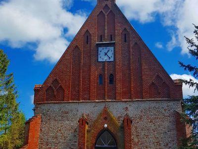 Zdjęcie przedstawia główne wejście do kościoła w Malechowie wraz z zegarem.