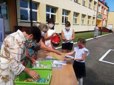 Zdjęcie przedstawia przedszkolaka i grono pedagogiczne ZS Ostrowiec podczas zakończenia roku szkolnego.