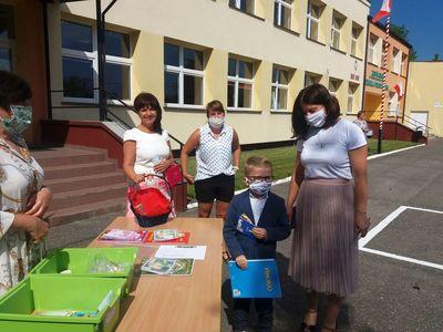 Zdjęcie przedstawia przedszkolaka z mamą i grono pedagogiczne ZS Ostrowiec podczas zakończenia roku szkolnego.