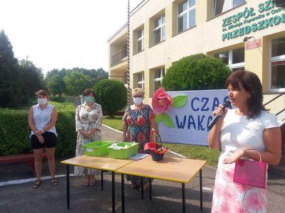 Zdjęcie przedstawia przemawiająca dyrektor Barbarę Chylewską i wychowawczynie z przedszkola w tle.