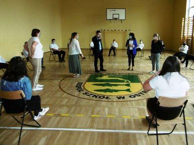 Zdjęcie przedstawia dyrektor, nauczycieli i ośmioklasistów w sali gimnastycznej przed egzaminem.