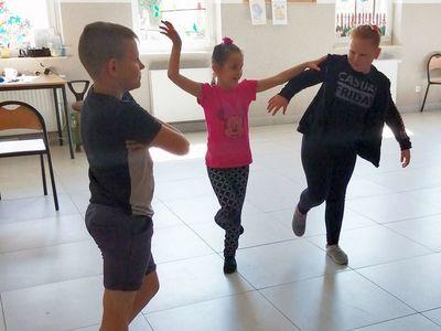 Zdjęcie przedstawia dzieci w tańcu podczas zajęć dziennikarsko - teatralnych na sali w Kusiach.