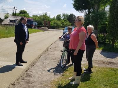 Zdjęcie przedstawia wójta Radosława Nowakowskiego podczas rozmowy z sołtys i mieszkankami Bartolina w miejscu remontowanej drogi gminnej.