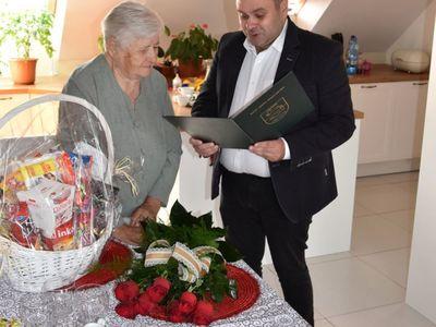 Zdjęcie przedstawia wójta Radosława Nowakowskiego odczytującego list gratulacyjny oraz Jubilatkę Zofię Galek z Malechowa.