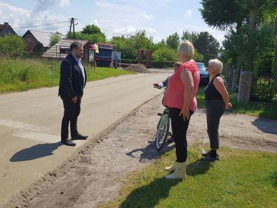 Zdjęcie przedstawia wójta Radosława Nowakowskiego podczas rozmowy z mieszkańcami Bartolina i sołtys Katarzyną Kozioł.