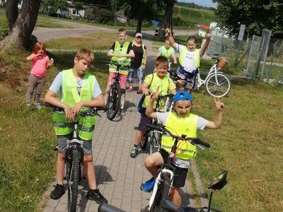 Zdjęcie przedstawia dzieci z Placówki Wsparcia Dziennego w Kusicach wraz z opiekunami podczas rajdu rowerowego do Sierakowa,