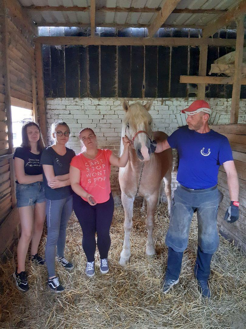 Zdjęcie przedstawia wychowanków Placówki Wsparcia Dziennego w Paprotach w stajni z koniem i kowalem, gdzie zostali zaproszeni.