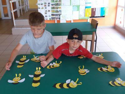 Zdjęcie przedstawia dwóch wychowanków Placówki Wsparcia Dziennego w Laskach eksponujących wykonane pszczoły z papieru.