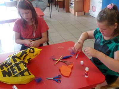 Zdjęcie przedstawia dwie wychowanki Placówki Wsparcia Dziennego w Laskach wykonujące prace plastyczne.
