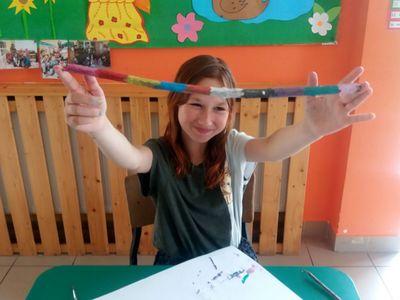 Zdjęcie przedstawia wychowankę Placówki Wsparcia Dziennego w Laskach, która wykonała korale z plasteliny.