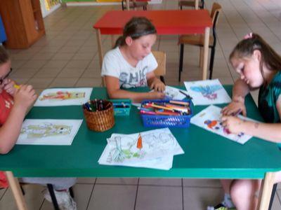 Zdjęcie przedstawia wychowanki Placówki Wsparcia Dziennego w Laskach wykonujących prace plastyczne.
