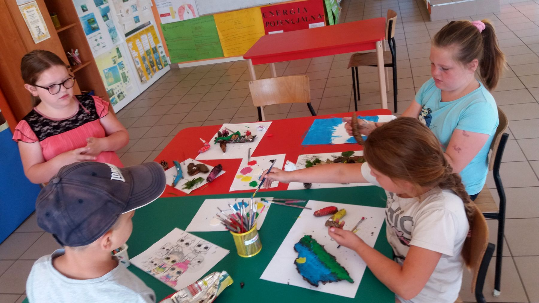 Zdjęcie przedstawia wychowanków Placówki Wsparcia Dziennego w Laskach wykonujących prace plastyczne.