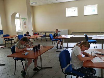 Zdjęcie przedstawia wychowanków Placówki Wsparcia Dziennego w Pękaninie, wykonujących prace plastyczne.