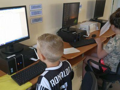 Zdjęcie przedstawia wychowanków Placówki Wsparcia Dziennego w Pękaninie przy stanowiskach komputerowych w świetlicy.