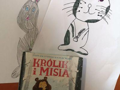 """Zdjęcie przedstawia prace plastyczne i książkę """"Królik i Misia""""."""