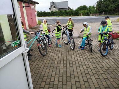 Zdjęcie przedstawia wychowanków Placówki Wsparcia Dziennego w Pękaninie przed świetlicą, gotowych do przejażdżki rowerowej.