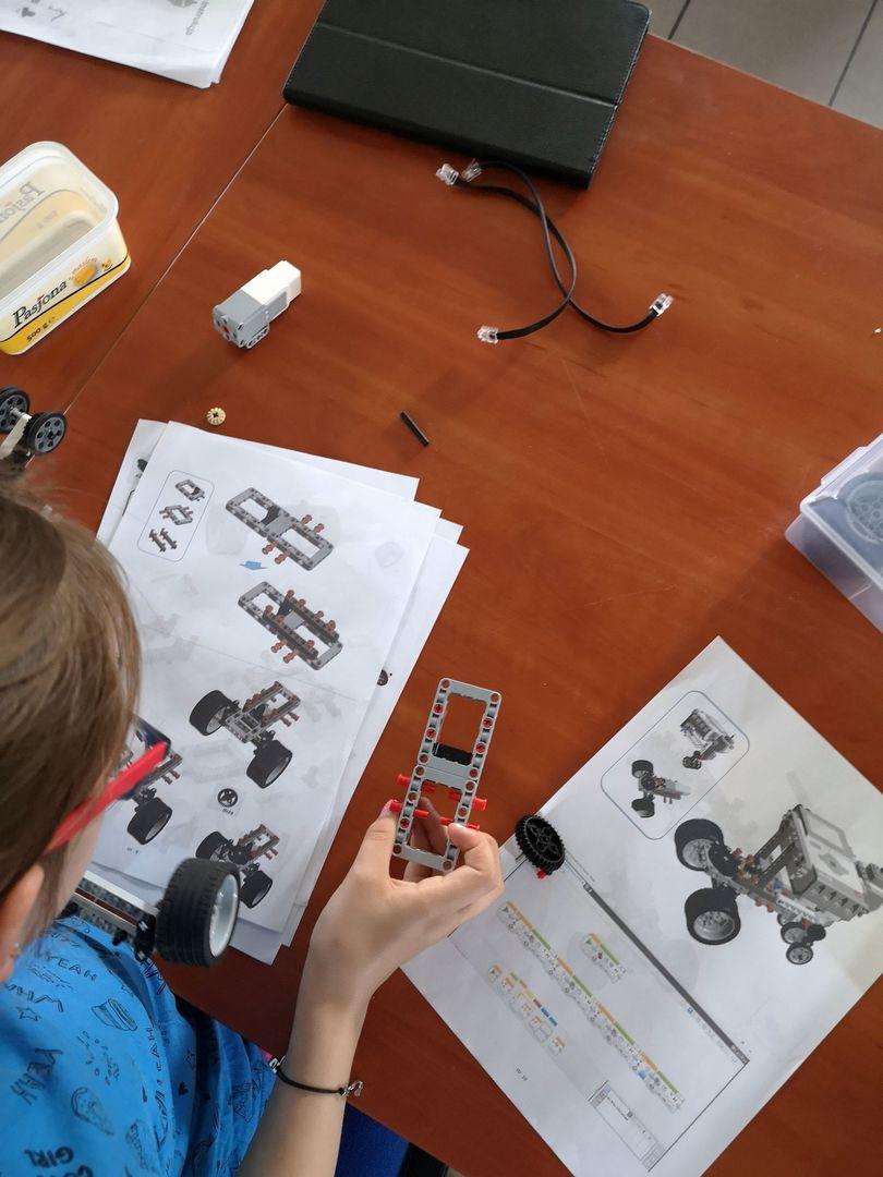 Zdjęcie przedstawia części do złożenia robota wraz z instrukcją i głowę wychowanki Placówki Wsparcia Dziennego w Pękaninie, pracującego nad zbudowaniem robota.