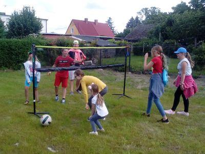 Zdjęcie przedstawia grupę wychowanków Placówki Wsparcia Dziennego w Ostrowcu grających w minisiatkówkę.