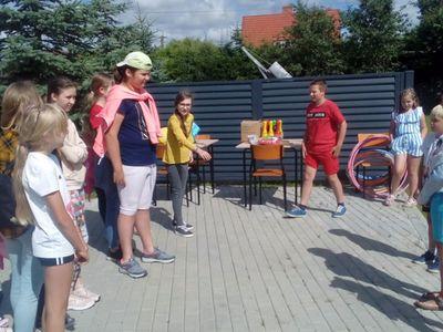Zdjęcie przedstawia grupę wychowanków Placówki Wsparcia Dziennego w Ostrowcu na dworze podczas gier i zabaw.