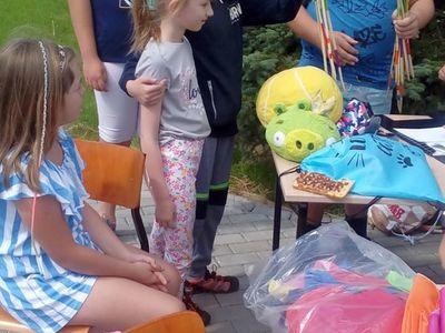 Zdjęcie przedstawia grupę wychowanków Placówki Wsparcia Dziennego w Ostrowcu na dworze, przygotowujących się gier i zabaw