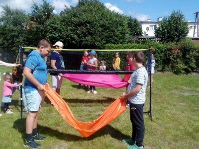 Zdjęcie przedstawia grupę wychowanków Placówki Wsparcia Dziennego w Ostrowcu , którzy uczestniczą w plenerowych grach i zabawach.