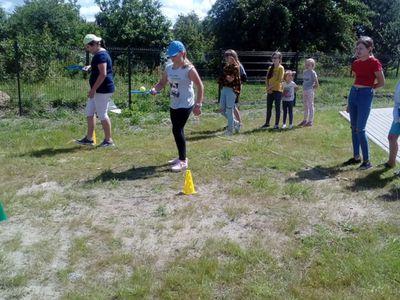 Zdjęcie przedstawia grupę wychowanków Placówki Wsparcia Dziennego w Ostrowcu , którzy uczestniczą w biegu z paletkami i piłeczkami.