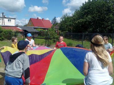 Zdjęcie przedstawia grupę wychowanków Placówki Wsparcia Dziennego w Ostrowcu  podczas zabawy z chustą klanza.