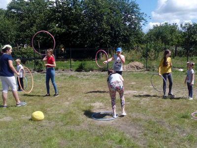 Zdjęcie przedstawia grupę wychowanków Placówki Wsparcia Dziennego w Ostrowcu podczas zabawy z hula hop.