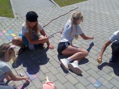 Zdjęcie przedstawia dziewczynki z Placówki Wsparcia Dziennego w Ostrowcu, które rysują kredą.