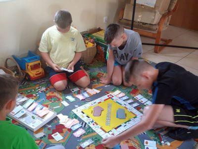 Zdjęcie przedstawia wychowanków Placówki Wsparcia Dziennego w Kosierzewie podczas gry w gry planszowe.
