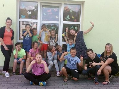 Zdjęcie przedstawia grupę dzieci z Placówki Wsparcia Dziennego w Laskach podczas wraz z wychowawczyniami i animatorem przed świetlicą wiejską.