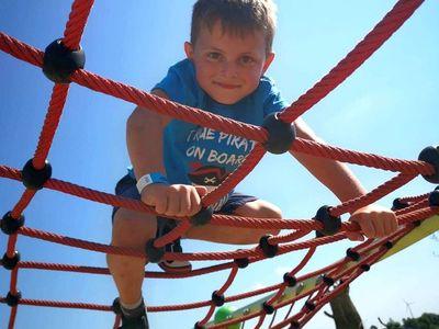 Zdjęcie przedstawia wspinającego się wychowanka Placówki Wsparcia Dziennego z Kusic w parku rozrywki Pomerania.