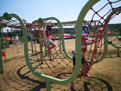 Zdjęcie przedstawia wspinające się dziewczynki z Placówki Wsparcia Dziennego z Kusic w parku rozrywki Pomerania.