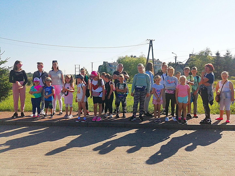 Zdjęcie przedstawia grupę wychowanków Placówki Wsparcia Dziennego z Kusic wraz z opiekunami przed parkiem rozrywki Pomerania.