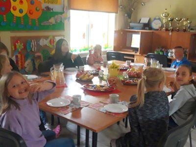 Zdjęcie przedstawia wychowanków Placówki Wsparcia Dziennego z Kosierzewa jedzących pizzę przy stole w świetlicy.