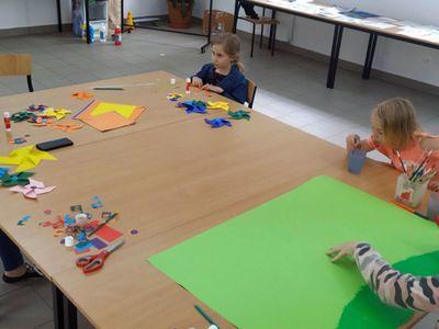 Zdjęcie przedstawia wychowanków Placówki Wsparcia Dziennego z Gorzycy oraz mamę jednego z dzieci, którzy przygotowują wspólnie  kolorowe wiatraki w świetlicy.