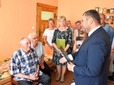 Zdjęcie przedstawia Jubilata Stanisława Filipiaka z Pękanina z rodzinką i wójta Radosława Nowakowskiego odczytującego list gratulacyjny.