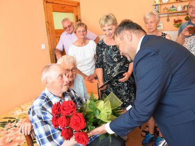 Zdjęcie przedstawia wójta Radosława Nowakowskiego wręczającego kwiaty na ręce Jubilata Stanisława Filipiaka z Pękanina. W tle rodzinka Jubilata.