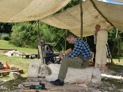 Zdjęcie przedstawia dwóch rzeźbiarzy, którzy w drewnie rzeźbią figurę, jeden na pierwszym planie, drugi w tle.