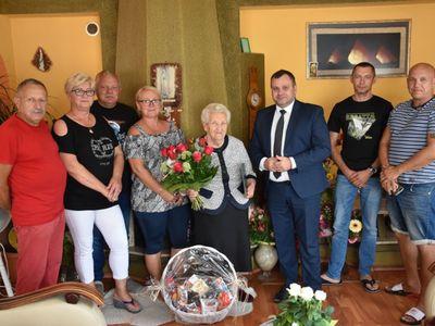 Zdjęcie grupowe przedstawia Jubilatkę, Panią Marię Musielaniec w obecności wójta Radosława Nowakowskiego oraz jej synów i rodziny.