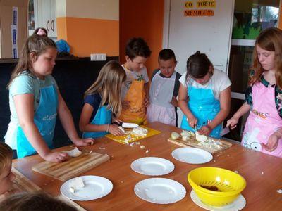Zdjęcie przedstawia wychowanków PWD Laski podczas krojenia warzyw na  zapiekankę w ramach zajęć kulinarnych.