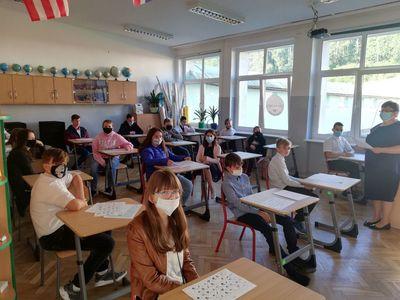 Zdjęcie przedstawia uczniów ze szkoły w Lejkowie z nauczycielem, którzy znajdują się w klasie.
